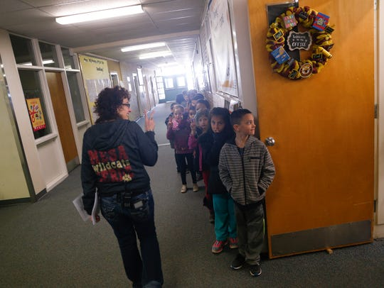 Mesa Verde Elementary School Principal Pamela Schritter greets her students on Friday at her school in Farmington.