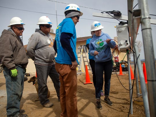 Berlyn Hubler, right, of GRID Alternatives, works on the electrical system for a solar panel project on Wednesday at the Ojo Encino Chapter house.