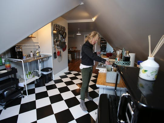 Dana McMahan creates a welcome sign in the kitchen of her Airbnb in Old Louisville.  Mar. 15, 2018