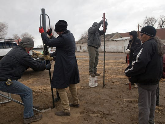 Volunteers and members of Issachar Calling build a fence on a chilly Sunday during repair work at the Healing Circle Drop-In Center's garden area in Shiprock.