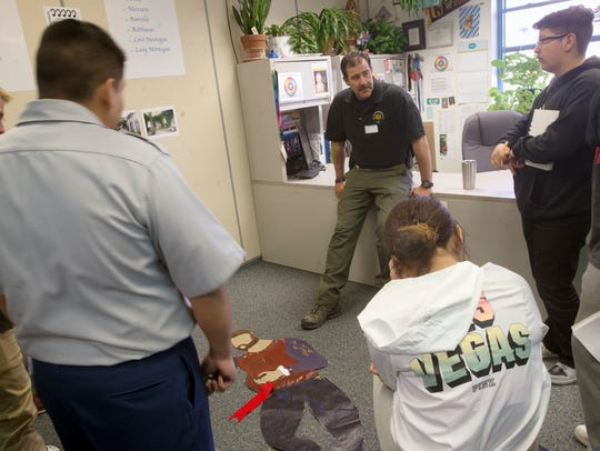 San Juan County Sheriff's Office Sgt. Dave McCall talks with Piedra Vista High School students near a simulated crime scene Wednesday at Piedra Vista High School in Farmington.