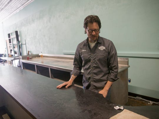 Tales of Tomorrow and Cosmic Cafe co-owner Steve Clark looks over a countertop that will be used for the planned coffee shop Wednesday in Farmington.
