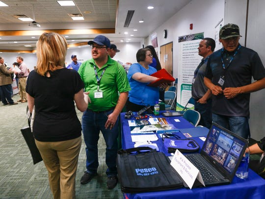 At center, Tim Grant, a field service supervisor with Process Equipment & Service Co, PESCO, talks about his company with interested job seekers Friday during a community job fair at San Juan College in Farmington.