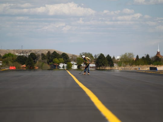 An airport employee works on a runway Tuesdayat the Four Corners Regional Airport in Farmington.