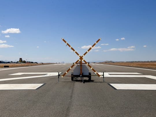 A lighted X closes a runway to traffic as workers finish a reconstruction project Tuesday at the Four Corners Regional Airport in Farmington.