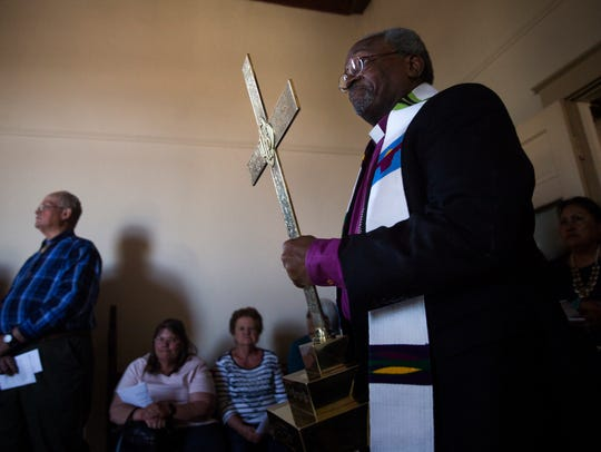 The Most Rev. Michael Curry, leader of the Episcopal Church, carries a crucifix to the altar on Wednesday at the Episcopal Church in Navajoland in Farmington.