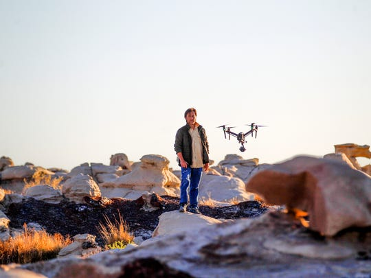 """Carlos Sanchez, a crew member with the """"Cosmos"""" production crew, stands in for a shot framed by a drone Monday in the Bisti/De-Na-Zin Wilderness area south of Farmington."""