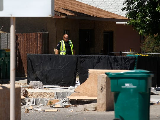 A Farmington police officer helps secure the scene where a woman was struck and killed by a car Thursday in the 700 block of West Apache Street in Farmington.