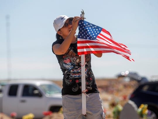 Kershena Hosteen works on fixing a flag Monday at the gravesite of a family member during a Memorial Day event at the Shiprock Veterans Memorial Cemetery.