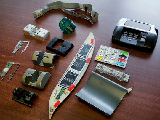 In this April 18, 2018, photo, a variety of tools used to skim information from credit cards are displayed at the office of the New York Police Department's Financial Crimes Task Force. The U.S. Secret Service says more than a billion dollars is stolen from U.S. consumers each year by credit card skimmers, money that funds organized crime and which is usually passed back to consumers through higher fees.