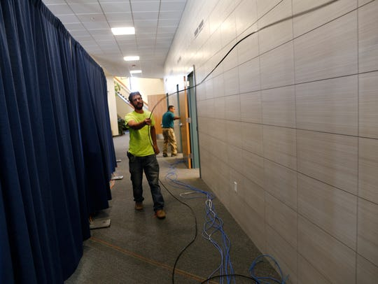 Kyle Chivers, a cable technician with DB Tech Inc. installs fiber-optic lines Wednesday during an expansion project at the Farmington Civic Center.