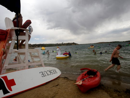 A life guard watches The Beach swimming area Thursday under threatening skies at Farmington Lake, which stores Animas River water for city use.