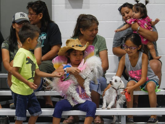 At center, Shineal Nakai adjusts her dog Ariel's costume Friday during the Kids Dog Show at the Farmington Recreation Center.