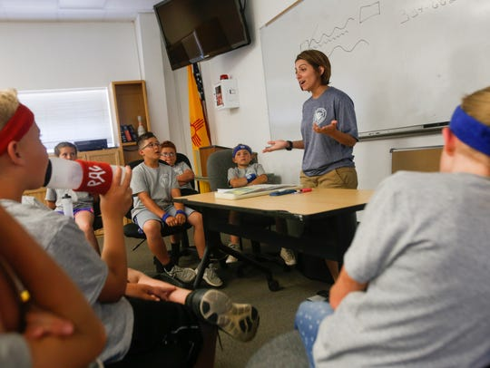Crystal Arellano, a lead floor supervisor with the San Juan County Communications Authority, talks with cadets from the Junior Law Enforcement Academy Thursday about emergency and nonemergency calls at Safety City in Kirtland.