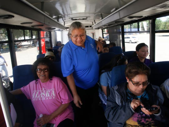 Navajo Transit System bus driver Jeanne Begay-Yazzie checks on passengers Monday before driving her bus at the Shiprock Chapter house.