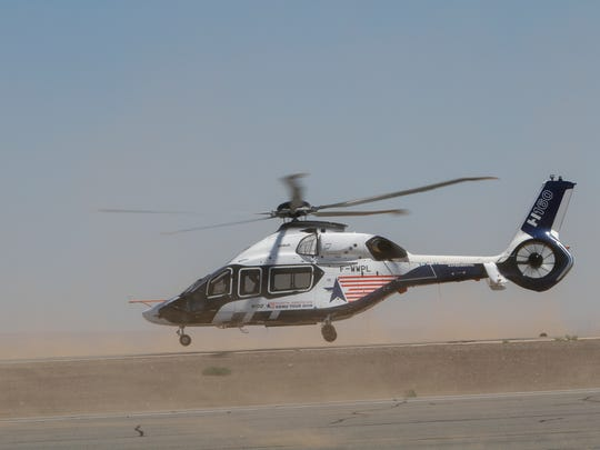 An Airbus H160 helicopter flies down the runway Tuesday