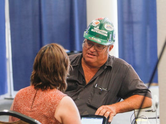 Pat Walters gives an oral statement to court reporter Ana Gallegos Tuesday during a public meeting organized by the federal Office of Surface Mining Reclamation and Enforcement at the Farmington Civic Center.