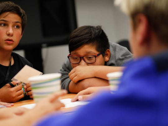 Corbin Coffman, left, and Isaiah Harrison work with their team to solve a puzzle Monday during the GenCyber Student Camp at San Juan College Quality Center For Business in Farmington.