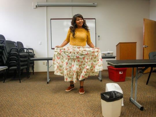 Jaime Begay of Coalmine Canyon, Arizona, shows her dress to her classmates Sunday during a Navajo skirt-making workshop hosted by the Office of Miss Navajo Nation and the Navajo Cultural Arts Program at Diné College's north campus in Shiprock.
