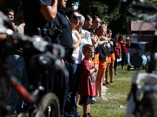 Lincoln Cole, center, stands with his mother Sommar Cole during the singing of the national anthem Tuesday during Aztec's National Night Out event at Minium Park.