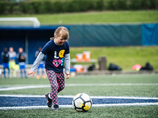 """Devin Fleming, daughter of Xavier men's soccer coach Andy Fleming, kicks a soccer ball before the start of """"Devin's Game,"""" an annual fundraiser for the Down Syndrome Association of Greater Cincinnati. Xavier hosts Northwestern Saturday night in the 8th annual Devin's Game."""
