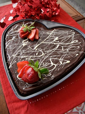 Becky Telfair placed sliced strawberries on her spiced brownie cake Thursday, Feb. 2, as she creates easy Valentine's Day desserts.
