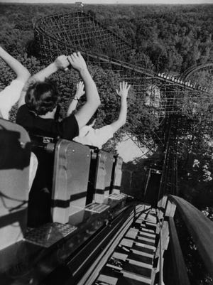 In this image from 1980, riders on The Beast hold their hands high as they drop down the first hill into an underground tunnel. Photo from Kings Island.