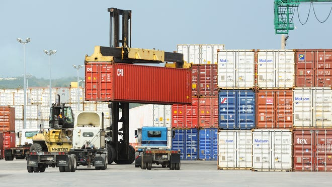 A top-lifter container handler transports a shipping container in the storage yard of the Port Authority of Guam on Cabras Island on Monday, Aug. 3.