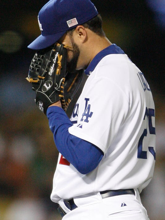FILE - In this Sept. 11, 2007, file photo, Los Angeles Dodgers pitcher Esteban Loaiza reacts after giving up his third home run in the third inning against the San Diego Padres during their baseball game in Los Angeles. Former Major League Baseball pitcher Esteban Loaiza has been arrested in California on suspicion of smuggling cocaine and heroin. The San Diego County Sheriff's Department says Loaiza was booked into jail Friday, Feb. 9, 2018,  evening and held in lieu of $200,000 bail. (AP Photo/Gus Ruelas, file)