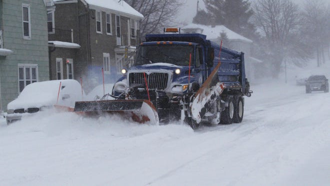A plow driver clears freshly fallen snow from a street near downtown Sheboygan on Monday, Jan. 15. A snowstorm dropped several inches across most of Wisconsin, though areas along the Lake Michigan shoreline were particularly hard hit.