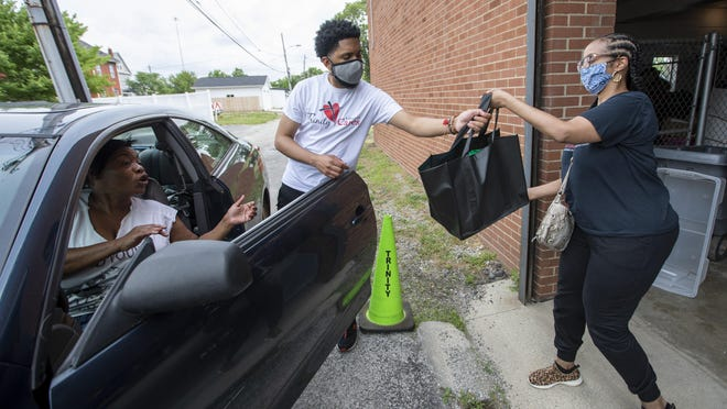 Volunteer Brandy Williams of Reynoldsburg hands TauVaughn Toney, the minister of children, teens and young adults at Trinity Baptist Church, bags of food, personal hygiene products and household items to put into the car of Tina Johnson at the King-Lincoln District church on Saturday, June 27, 2020. Johnson was picking up the items for family members who live in the neighborhood.