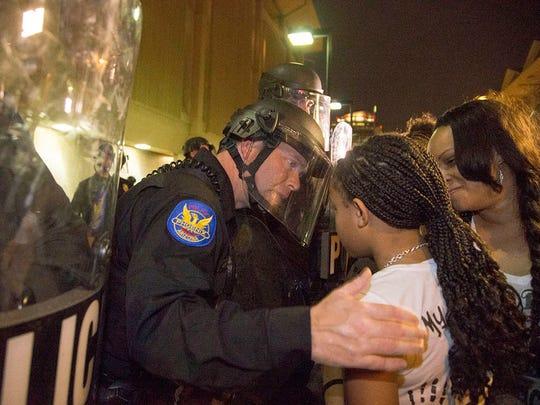 A Phoenix police officer talks to Rumain Brisbon's