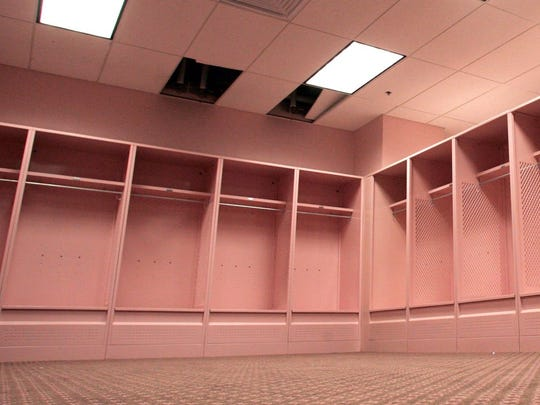 The visitors' locker room at Kinnick Stadium is pastel pink — pink walls, stalls, ceiling, carpet, urinals.