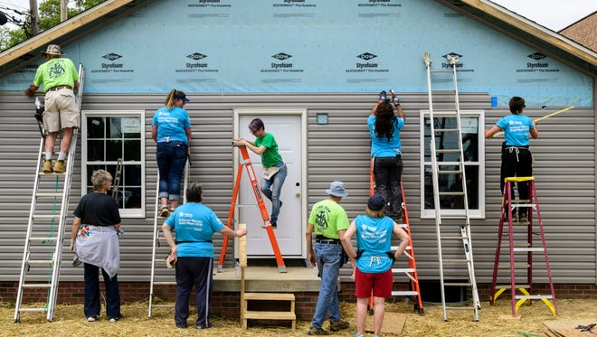 Habitat for Humanity volunteers participate in National Women Build Week by putting up siding on a new house located on N. 3rd Ave. in Evansville, Ind., Wednesday, May 9, 2018.