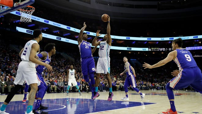 Charlotte Hornets' Dwight Howard, center right, goes up to shoot against Philadelphia 76ers' Joel Embiid, center left, during the first half of an NBA basketball game, Monday, March 19, 2018, in Philadelphia.