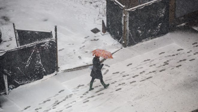 A woman carries an umbrella as she walks through the snow, April 2, 2018, on Atlantic Avenue in the Brooklyn borough of New York City.