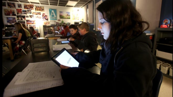 A student works on a tablet at Burns Middle School. Technology and internet access are concerns for some families preparing for virtual learning.