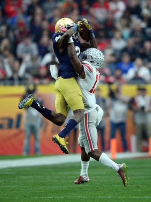 Eli Apple of Ohio State (right) breaks up a pass during the Fiesta Bowl against Notre Dame. The redshirt sophomore plans to enter the NFL Draft.