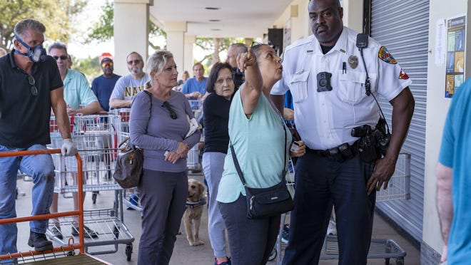 PALM BEACH GARDENS -- Palm Beach Gardens Police officer G. Allen listens to a Costco customer who was upset about what was the right line to stand at the store in March. People were flocking to stores to buy food and supplies due to the coronavirus outbreak.