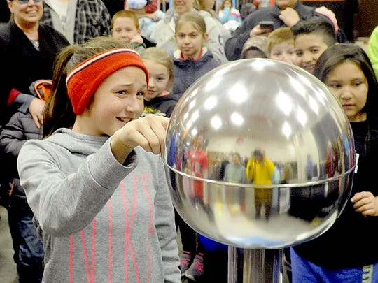 Fernley Intermediate School seventh-grader Ciara Pritchard gets a shock from a Van de Graph generator.