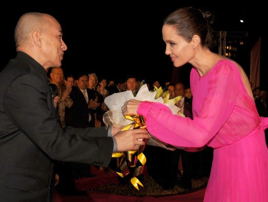 Cambodian King Norodom Sihamoni (L) gives flowers to