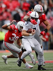 Ohio State defensive end Chase Young, right, sacks Penn State quarterback Will Levis during the second half of an NCAA college football game Saturday, Nov. 23, 2019, in Columbus, Ohio. Ohio State beat Penn State 28-17. (AP Photo/Jay LaPrete)