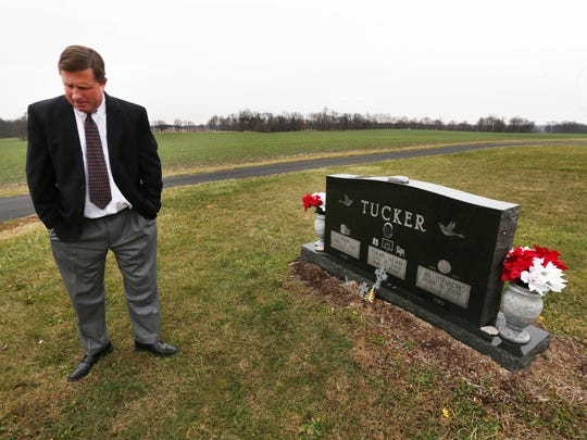 Brad Tucker stands beside the gravestone of his late brother, Chad Tucker, Butler University's all-time leading scorer, in Mannan Cemetery, located along a desolate country road several miles southeast of Cloverdale, on Monday, Dec. 22, 2014. The marker is engraved with Chad's Butler uniform number, 31, on a bulldog, and his high school number, 5, on a clover leaf.