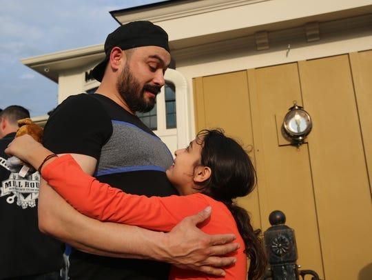 Ruben Berra hugs his 10-year-old daughter, Jazmine