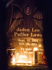 Jaden Laws' headstone is illuminated by candles during