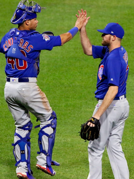 Chicago Cubs catcher Willson Contreras (40) celebrates with relief pitcher Wade Davis after the team's 1-0 win over the Pittsburgh Pirates in a baseball game in Pittsburgh, Tuesday, April 25, 2017. (AP Photo/Gene J. Puskar)