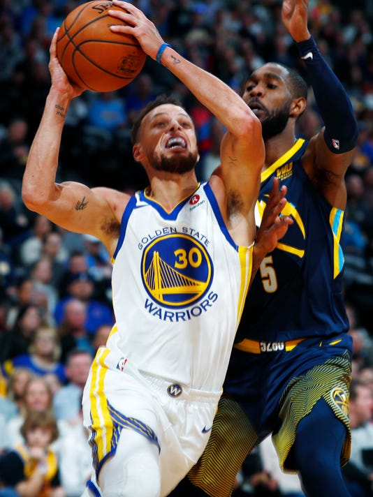Golden State Warriors guard Stephen Curry, left, drives to the basket past Denver Nuggets guard Will Barton in the first half of an NBA basketball game Saturday, Feb. 3, 2018, in Denver. (AP Photo/David Zalubowski)