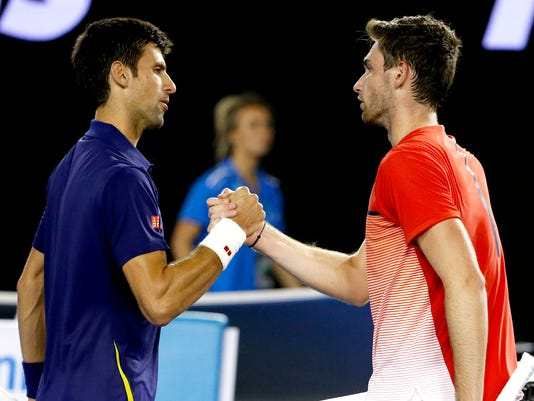 Novak Djokovic, left, of Serbia is congratulated by Quentin Halys of France after winning their second round match at the Australian Open tennis championships in Melbourne, Australia, Wednesday, Jan. 20, 2016.(AP Photo/Vincent Thian)