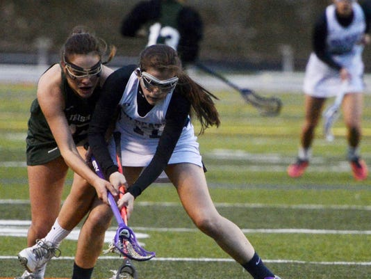 Kate Penn — GameTimePA.com York Catholic's Amanda Tufano, left, and Dallastown's Koby Duke go for the ball during Thursday's girls' lacrosse game at Dallastown. The Irish won, 13-2.