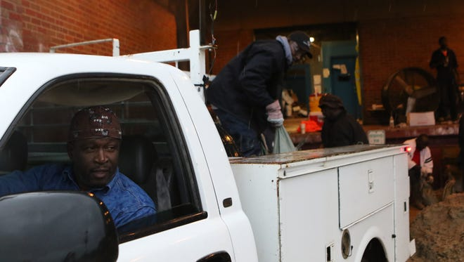 """Arthur White watches as employees from the Monroe Public Works Department load sandbags into the back of his truck on Wednesday. White said he had been waiting since 6 a.m. to pick up 50 bags he was taking to two houses off Winnsboro Road on the south side. """"It's going to get worse,"""" White said. """"I'm just volunteering to give my time to help someone."""""""